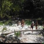 Escursionisti scarponi e costume in risalita sul torrente